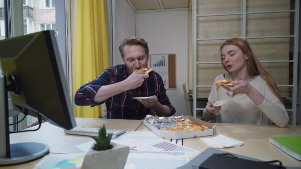 Thumbnail for Man And Woman Eating Pizza At Workplace