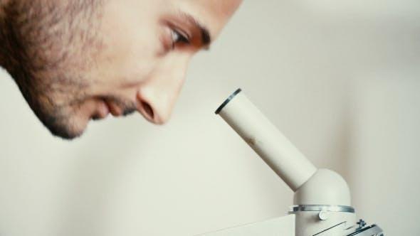 Thumbnail for Man Lookig Through Microscope