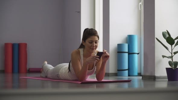 Girl Lying On The Yoga Mat And Looking At The Phone.
