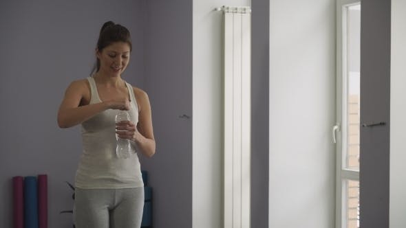 Thumbnail for Girl Drinks Water From a Bottle In a Gym