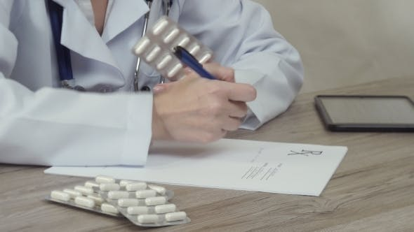 Thumbnail for He Doctor Looks At Tablets And Writes a Prescription.