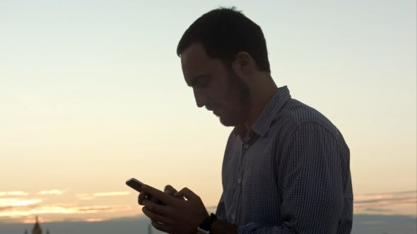 Thumbnail for Businessman With Smartphone At Sunset