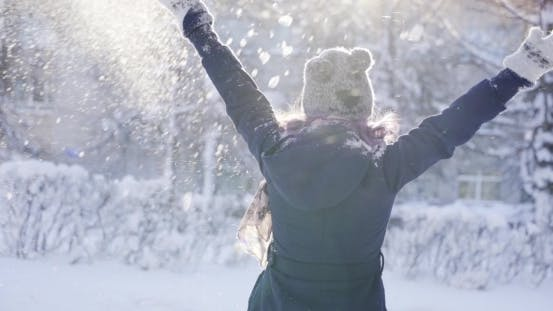Thumbnail for Happy Girl Throws Snow Up At Sunny Day