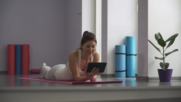 Woman Lying On a Yoga Mat And Looking At The Tablet
