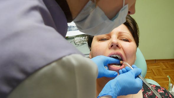 Thumbnail for Young Woman With Dentist Pulling Tooth