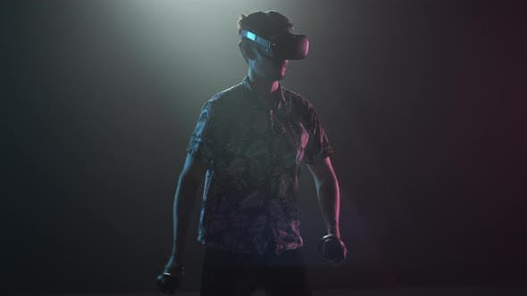 Male Gamer In VR Headset Using Controllers