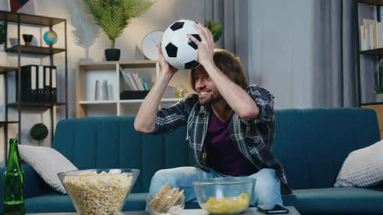 Guy Rejoicing from Scored Goal with Shouts when Watching Football Match on TV at home