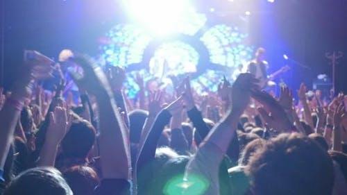 Menschen klatschen bei Konzert in die Hände