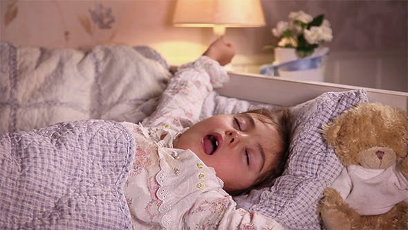 Little Girl Gives Yawn In Her Bed