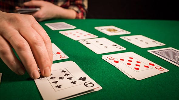 Female Hands Holding Cards And Playing Solitaire
