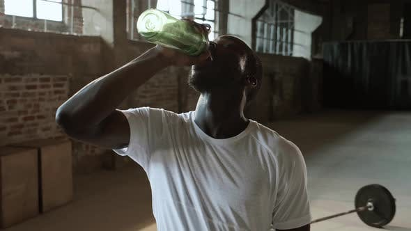Man drinking water from sport bottle after workout at gym