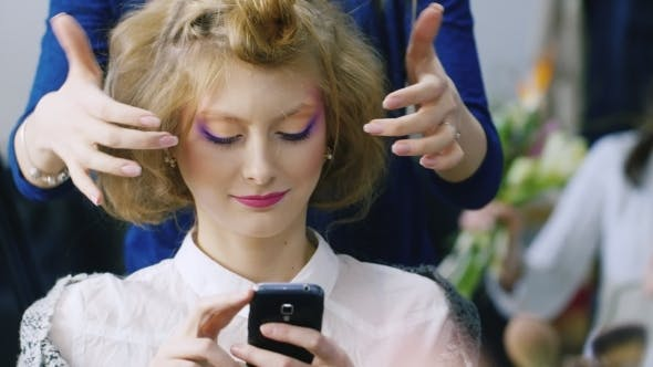 Cover Image for Beautiful Woman Enjoys The Smartphone In a Beauty Salon