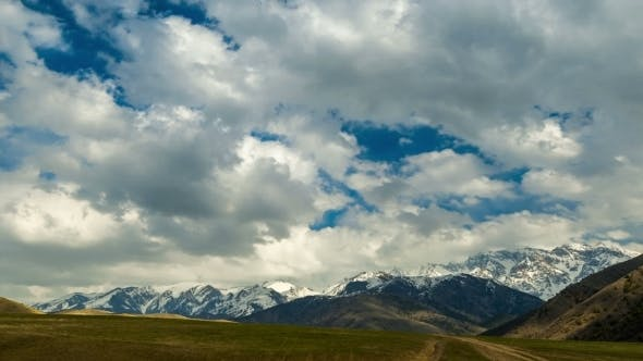 Cover Image for Clouds Over Autumn Field With a View Of Mountains