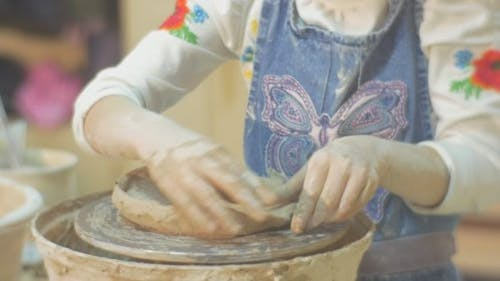 Kid is Molding an Edges of Clay Circle Sculpting