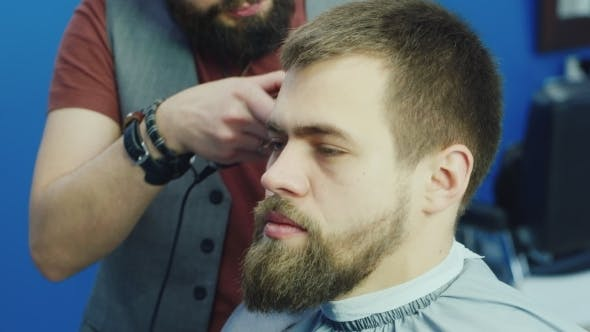 Cover Image for Male Barber At Work, Doing Hairstyle Young Man