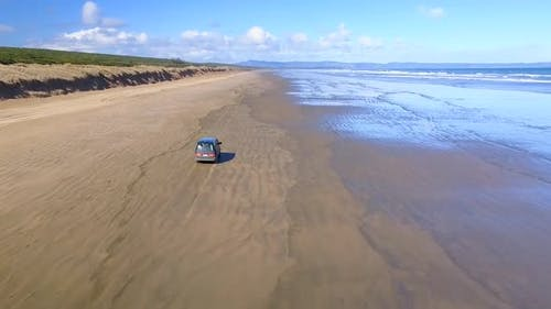 Driving a van on the beach by the sea