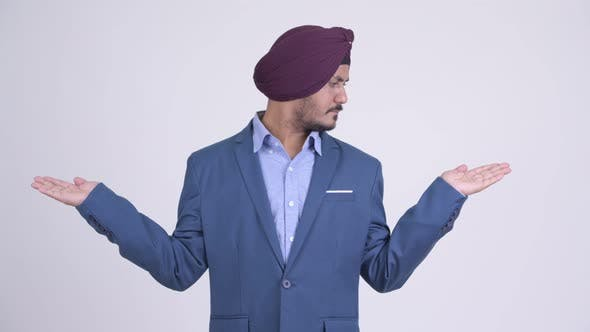 Thumbnail for Bearded Indian Sikh Businessman Comparing Something