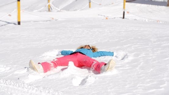 Thumbnail for Young Woman Making a Snow Angel In White Snow