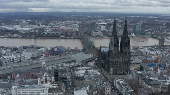 AERIAL: Wide Shot of Cologne Germany From the Air with Majestic Cathedral on Cloudy Day