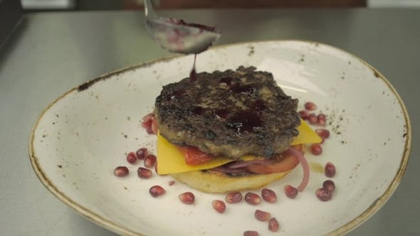 Home Made Pomegranate Sauce Being Spooned Onto a Burger