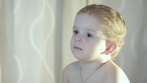 Child Watches On TV Screen,with Glow From Screen On His Face