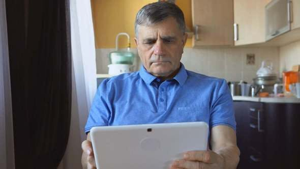 Thumbnail for An Aged Man Sits And Uses A Tablet PC At Home