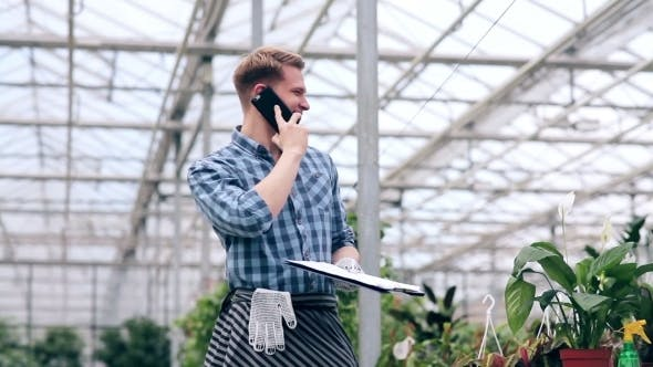 Thumbnail for Young Man Talking On The Phone In Greenhouse.