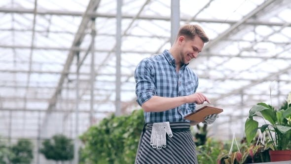 Thumbnail for Cheerful Florist With Tablet In Greenhouse