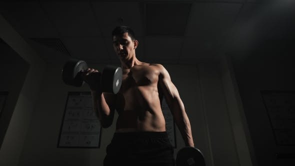 Thumbnail for Handsome Muscular Man Working Out With Dumbbells Over Dark Background