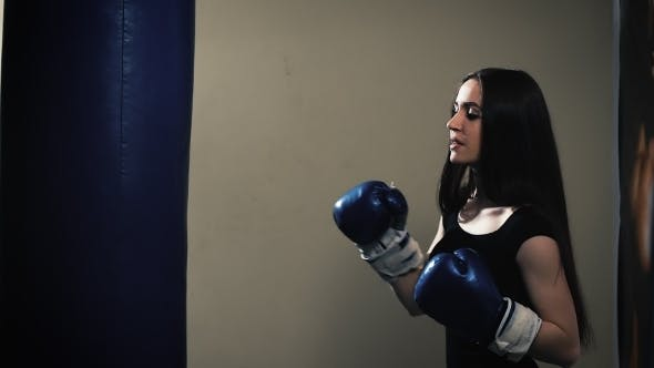 Thumbnail for Attractive Female Punching A Bag With Boxing Gloves On