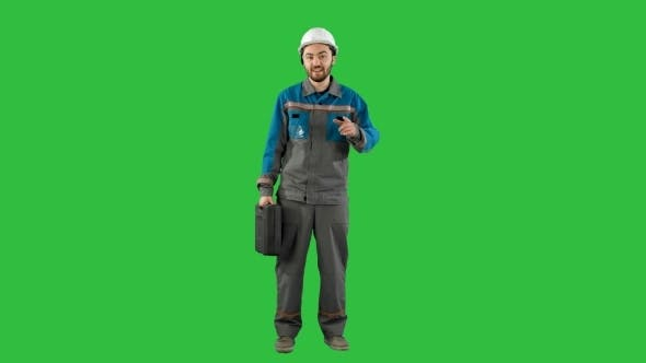 Thumbnail for Builder In Helmet With a Suitcase Says On Camera On a Green Screen, Chroma Key.