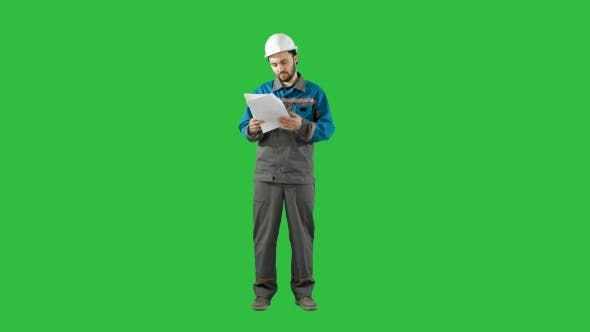 Thumbnail for Engineer Man Verify And Read Files Documents On a Green Screen, Chroma Key.