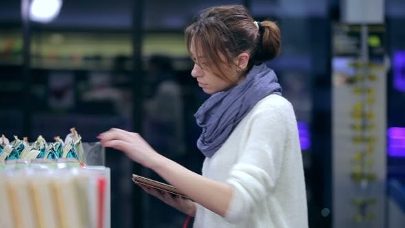 Thumbnail for Pretty Girl Browses Shopping List On The Tablet
