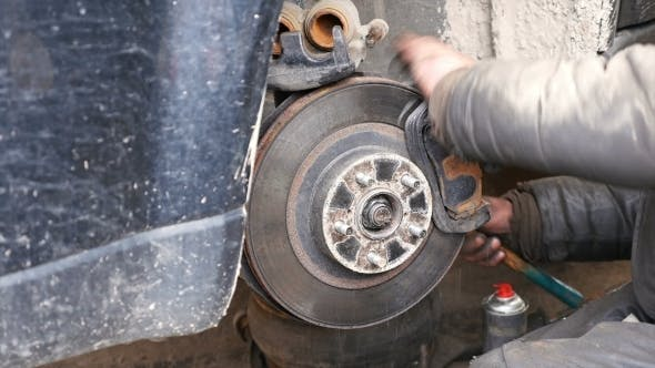 Cover Image for Auto Mechanic Working On Brakes In Car Repair Shop