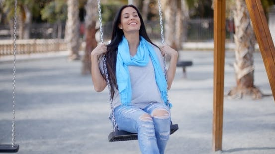 Happy Young Woman Relaxing On a Swing