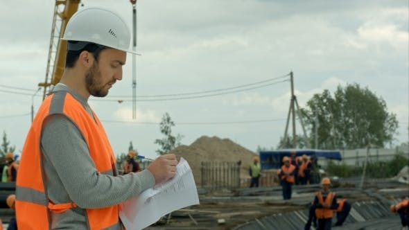 Thumbnail for Attractive Architect Is Planning To Build a Construction. He Is Standing And Holding a Blueprint