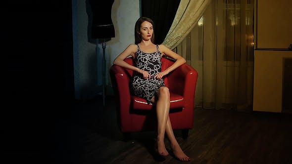 Thumbnail for Young Woman Sitting In Red Armchair