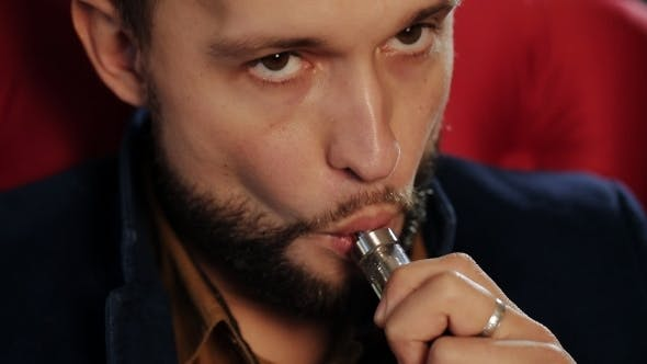 Thumbnail for Brutal Guy With a Beard Smokes An Electronic Cigarette In a Red Armchair