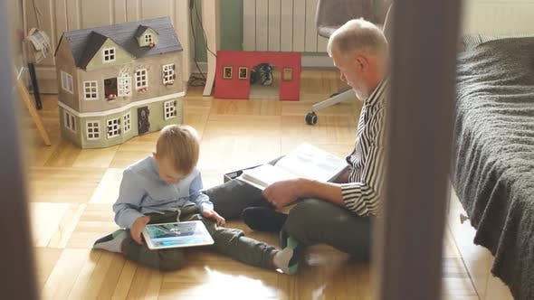 Thumbnail for Grandpa Looks Photo Album with His Wedding, Little Boy Using Electronic Tablet