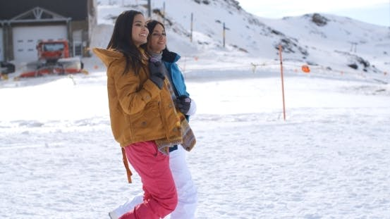 Thumbnail for Two Young Women Walking Through Snow At a Resort