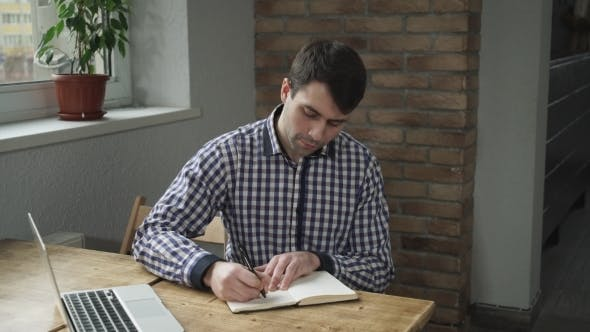Thumbnail for Attractive Man In a Shirt Making Notes In a Diary And Looking At a Laptop.