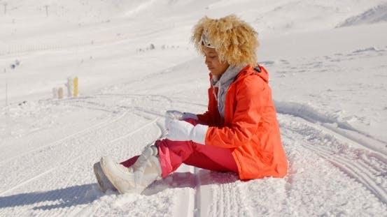 Thumbnail for Woman In Orange Snowsuit Sitting On Ski Slope