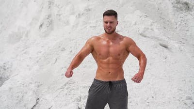 Spots man standing in pose. Well built bodybuilder posing in the mountains