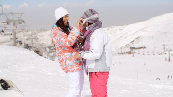 Thumbnail for Young Woman Adjusting Her Friends Ski Goggles