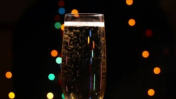 Thumbnail for Bubbles Inside a Glass Of Champagne Against The Background Of Holiday Lights