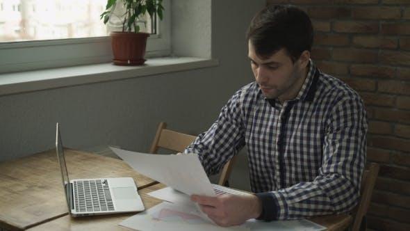 Thumbnail for Ein Mann schaut auf den Tisch und macht eine Notiz im Notizbuch.