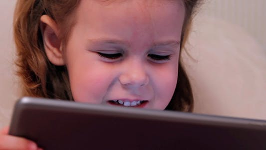 Thumbnail for Little Girl Watching a Cartoon on the Electronic Tablet