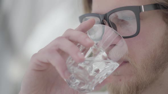 Thumbnail for Close Up Portrait of Blond Bearded Thoughtful Man in Glasses Drinking Water From the Glass Close Up