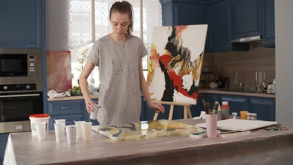Thumbnail for Young Woman Pouring Paint on Canvas while Creating Fluid Painting