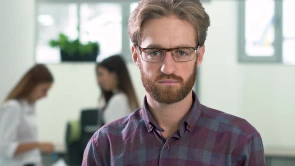 Thumbnail for Portrait of a Bearded Guy in Glasses and in a Casual Plaid Shirt Standing in the Office Center in